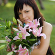Stock Photo: Beautiful young woman with lilies