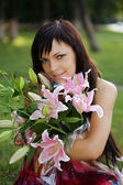 Beautiful young woman with lilies — Stock Photo