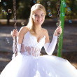 Beautiful young bide on a swing — Stock Photo