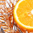 Orange in New Year's tinsel — Stock Photo