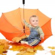 图库照片: Little boy sits in orange umbrella.