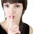 Girl has put finger to lips — Stock Photo