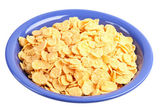 Corn-flakes on dark blue plate. — Stock Photo