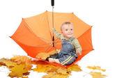 Little boy sits in orange umbrella. — Stock Photo