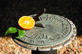 Tangerine with sundial — Stock Photo
