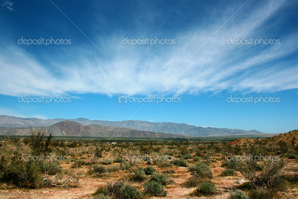 The dark blue sky with clouds over desert and mountains.  Stock Photo #2554025