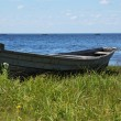 Old wooden boat on the lake bank - Stock Photo