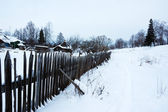 Snowy footpath near wooden fence — Stockfoto