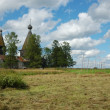 Stock Photo: Field with haystacks and wooden church