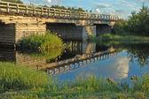 Old wooden bridge at sunset — Stock Photo