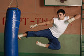 Kickboxer kicking the sandbag — Stock Photo