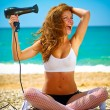 Stock Photo: Girl on beach with hair dryer