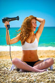 Girl on the beach with a hair dryer — Stock Photo