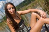 брюнетка молодая девушка, сидя на открытом воздухе — Стоковое фото