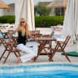Caucasian model sitting by a pool — Stock Photo #1811497