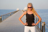 Model with bronze tan on a pier — Stock Photo