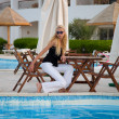 Caucasian young model sitting by a pool - Stock Photo