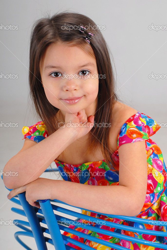 Portarit of a cute brown-haired girl wearing bright-colored dress and resting on a fancy chair — Stock Photo #1122792