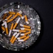 Ashtray full of cigarette butts - Stock Photo