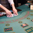 Croupier shuffling playing cards at poke — Stok fotoğraf
