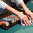 Croupier handling cards at poker table — Stok fotoğraf