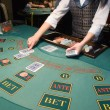 Croupier handling cards at poker table — Стоковая фотография