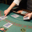 Croupier handling cards at poker table — 图库照片