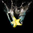 Starfruit tumbled into water, a lot of sparks and drops on black background, isolated — Stock Photo #1164333