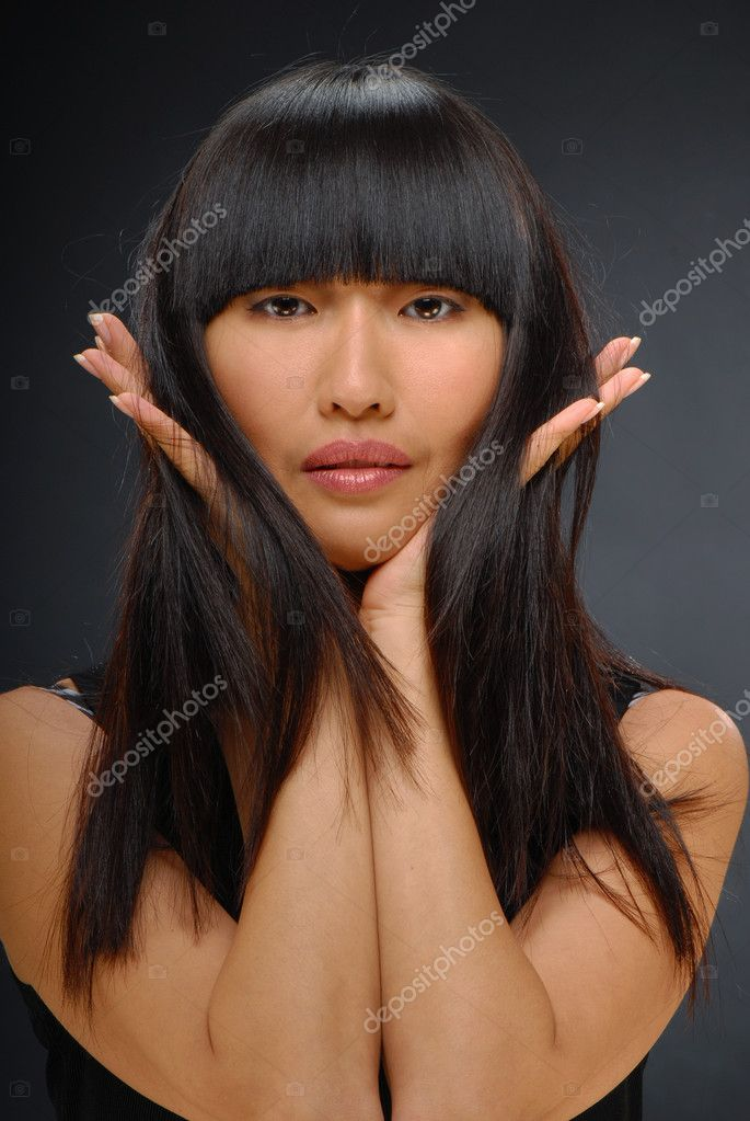 Close up portrait of a beautiful attractive Asian woman, holding her long black hair, on dark background — Stock Photo #1164370