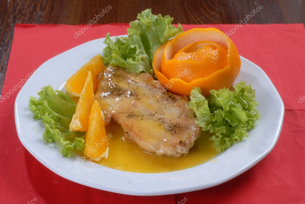 A plate of juicy pork chop with green salad, decorated with slices of orange and citron shaped as a rose — Stock Photo #1164464