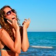 Young smiling woman talking by phone on — Stock Photo