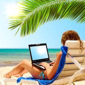 在海滩上的冲浪。便携式计算机的显示器是 — 图库照片