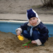 The child, playing to a sandbox - Stock Photo