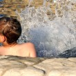 Boy kicking in pool — Stock Photo