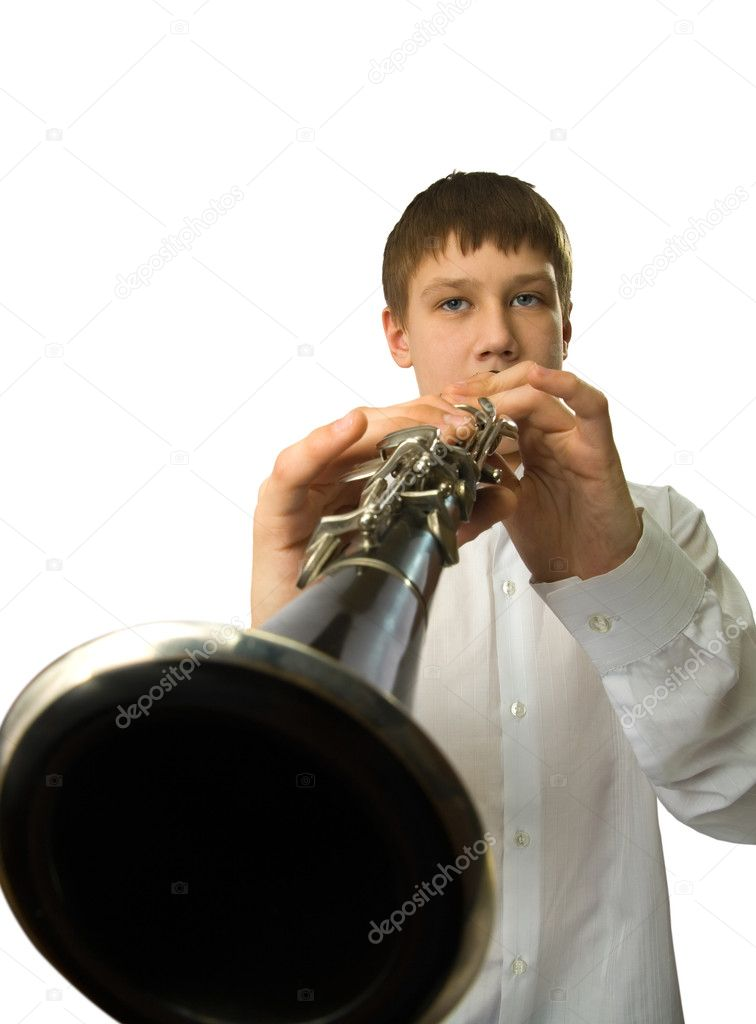 The teenager playing on a clarinet. The image on a white background.  Stock Photo #1114523