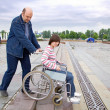 Man pushing woman in wheelchair — Stock Photo
