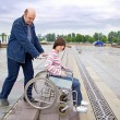 Man pushing woman in wheelchair - Stockfoto