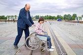 Толкая женщина человек в инвалидной коляске — Стоковое фото
