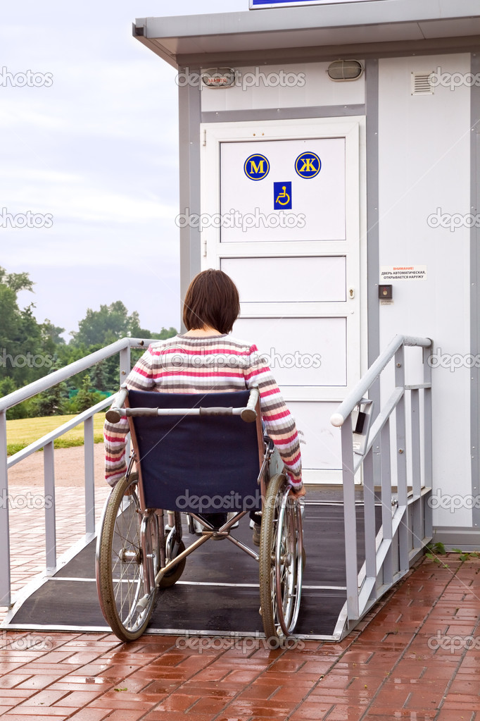 Woman in wheelchair drives to a toilet for invalids — Stock Photo #1121490
