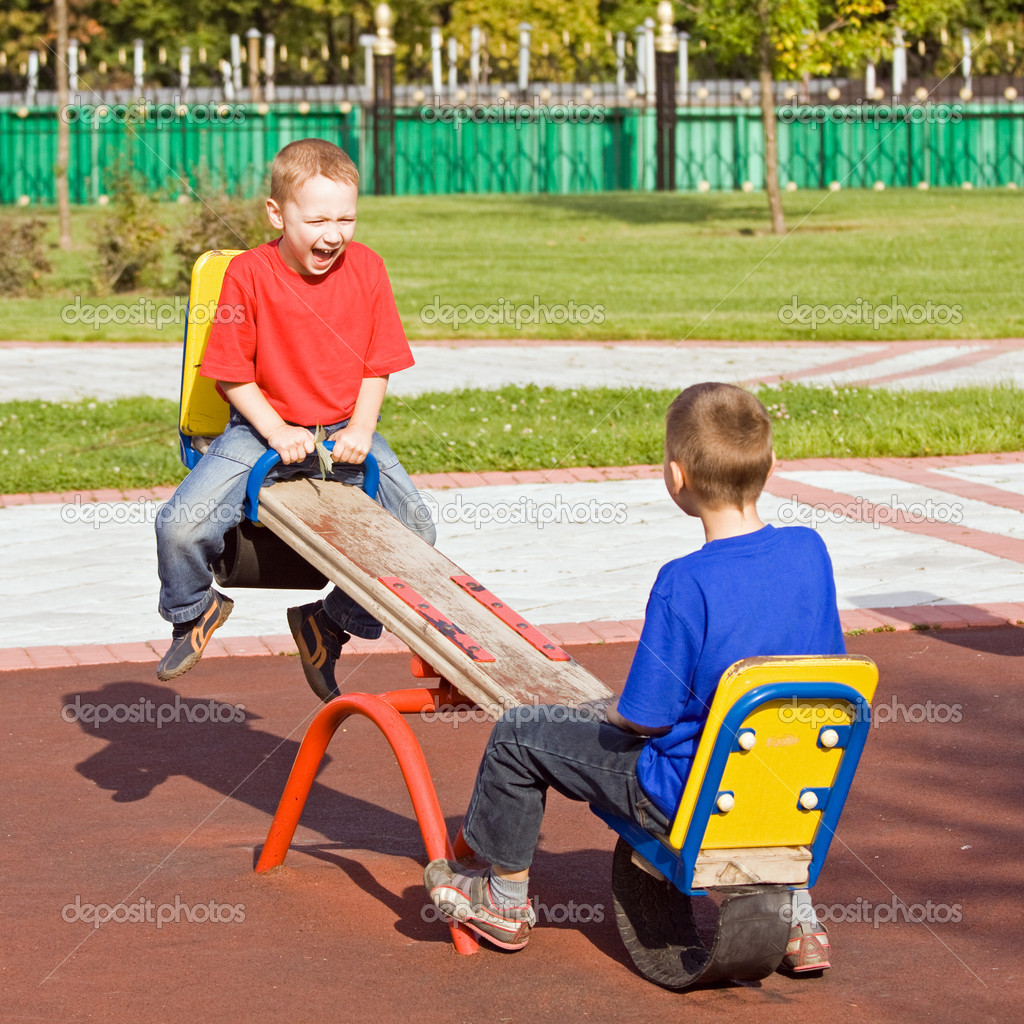 Boys playing on a seesaw on a playground in a sunny day — Stock Photo #1265250