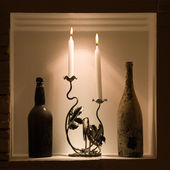 Ancient wine bottles with candles — Stock Photo