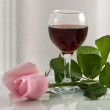 Stock Photo: Glass with wine and pink rose
