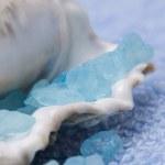 Marine salt, cockleshell and blue towel — Stock Photo