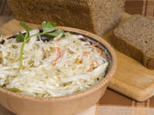 Cole-slaw and bread on a cook-table — Stock Photo