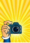 Camera in hand — Stock Vector