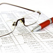 Financial report with pen and glasses — Stok fotoğraf