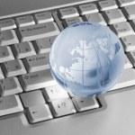 Blue glass globe on keyboard — Stock Photo