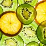 Kiwi fruit and orange in backlight — Stock Photo