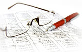Financial report with pen and glasses — Stock Photo