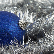 A blue Christmas ball in silver glare — Stock Photo